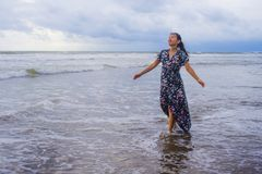 Portrait of young beautiful and happy Asian Chinese woman on her 20s or 30s wearing long chic dress walking alone on beach sea Royalty Free Stock Image