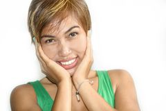 Portrait of young beautiful and happy Asian Singaporean or Malay woman smiling joyful with hands on her face isolated on white. Head and shoulders portrait of Royalty Free Stock Photo