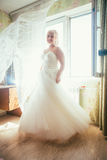 Portrait of young beautiful happy bride standing near a window.  Royalty Free Stock Photos
