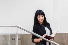 Portrait of Young Beautiful happy brunette woman dressed in a black business suit working with a notebook, standing in office,. Portrait of Young Beautiful happy royalty free stock photo