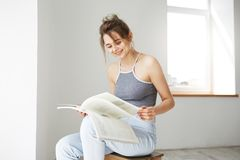 Portrait of young beautiful happy girl smiling reading book sitting on chair over white wall at home. Royalty Free Stock Image