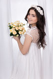 Portrait of young beautiful happy woman in white bridal dress wi. Th flowers standing near the window Royalty Free Stock Photos