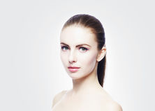 Portrait of young, beautiful and healthy woman: over cold grey background. Royalty Free Stock Images