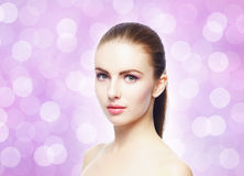 Portrait of young, beautiful and healthy woman: over pink background. Healthcare, spa, makeup and face lifting concept Stock Images