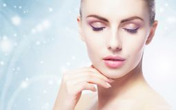 Portrait of young, beautiful and healthy woman: over winter background. Healthcare, spa, makeup and face lifting concept