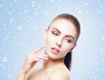 Portrait of young, beautiful and healthy woman: over winter background. Healthcare, spa, makeup and face lifting concept Royalty Free Stock Photo