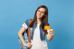 Portrait of young beautiful interested pleasant woman student in denim clothes, glasses with backpack hold credit card stock photo
