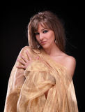 Portrait of a young beautiful lady. Covered with golden fabrics royalty free stock images