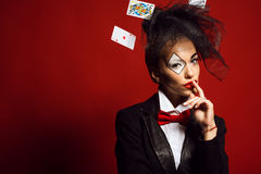 Portrait of a young beautiful lady croupier with an artistic make up in an image of joker Stock Image