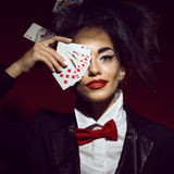 Portrait of a young beautiful lady croupier in an image of joker. Portrait of a young beautiful lady croupier with an artistic make up joker hiding her eye royalty free stock photography