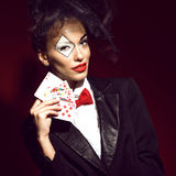Portrait of a young beautiful lady croupier in an image of joker. Portrait of a young beautiful lady croupier with an artistic make up joker holding playing Stock Photos