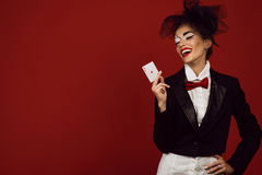 Portrait of a young beautiful lady croupier in an image of joker holding an ace card and laughing. Portrait of a young beautiful lady croupier with an artistic Stock Images