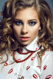 Portrait of a young beautiful lady with curly fair hair and provocative make-up looking straight Royalty Free Stock Photos
