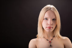 Portrait of a young beautiful lady with necklace isolated over b Royalty Free Stock Images