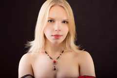 Portrait of a young beautiful lady with necklace isolated over b Stock Images