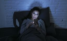 Portrait of young beautiful latin woman using mobile phone late night sleepless lying in bed in the dark in smartphone and interne. Portrait of young beautiful stock photography