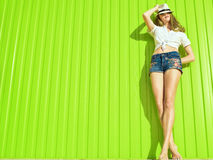 Portrait of young beautiful long-legged model in white tied up shirt, jeans shorts with flower ornament and panama. On her eyes standing at the bright light royalty free stock photo