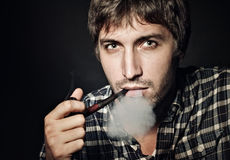 Portrait of the young beautiful man smoking a pipe Stock Photography