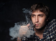 Portrait of the young beautiful man smoking a pipe Stock Photos