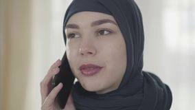 Portrait of a young beautiful muslim woman in black headdress talking by cell phone close up. Cute asian girl in head stock footage