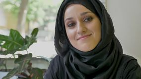 Portrait of young beautiful muslim woman in hijab sitting in cafe, looking forward and then in camera, smiling