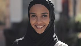 Portrait of young beautiful muslim woman wearing hijab headscarf laughing cheerful in the old city. Close up. stock footage