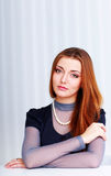 Portrait of a young beautiful pensive woman sitting Stock Image