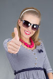 Young beautiful pinup girl in sunglasses thumbs up Stock Images