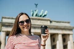 A person holds a disposable cup with coffee or another drink on the background of the Brandenburg Gate in Berlin. Portrait of a young beautiful positive smiling royalty free stock photo