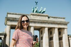 A person holds a disposable cup with coffee or another drink on the background of the Brandenburg Gate in Berlin. Portrait of a young beautiful positive smiling royalty free stock image