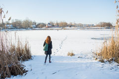 Portrait of a young beautiful red hair girl crossing frozen river Royalty Free Stock Photography