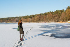 Portrait of a young beautiful red hair female crossing frozen river near forest Royalty Free Stock Photo