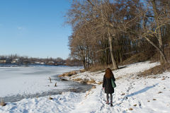 Portrait of a young beautiful red hair european girl walking near the frozen river. In Ukraine Stock Photo