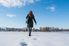 Portrait of a young beautiful red hair european girl walking on snowy frozen river. At winter Stock Photo