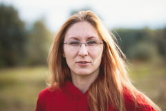 Portrait of the young beautiful red hair woman in a glasses walking in park. Telephoto Stock Photos