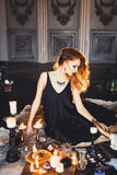 Portrait of young beautiful red-haired girl in the image of a Gothic witch on Halloween Royalty Free Stock Images