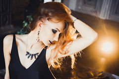 Portrait of young beautiful red-haired girl in the image of a Gothic witch on Halloween Stock Image