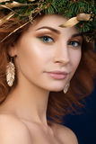 Portrait of young beautiful redhaired woman with firry wreath. With golden leaves in her hair. SPA or skincare concept Royalty Free Stock Images