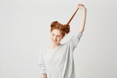 Portrait of young beautiful redhead girl untie bun touching hair over white background. Stock Photo