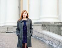 Portrait of young beautiful redhead lady in blue dress and grey coat  on the porch at winter outdoors Stock Photos
