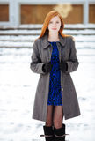Portrait of young beautiful redhead lady in blue dress and grey coat at winter outdoors Royalty Free Stock Photo