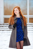 Portrait of young beautiful redhead lady in blue dress and grey coat at winter outdoors Royalty Free Stock Photos