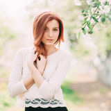 Portrait of young beautiful redhead woman in a garden Stock Photo