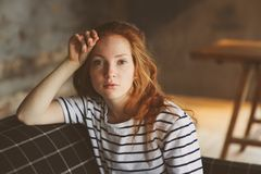 Portrait of young beautiful redhead woman relaxing at home in the autumn ot winter cozy evening Royalty Free Stock Photo