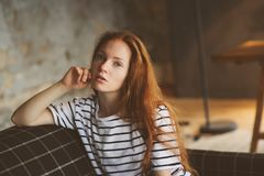 Portrait of young beautiful redhead woman relaxing at home in the autumn ot winter cozy evening Royalty Free Stock Images