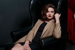 Portrait of young, beautiful sad woman with short brown hair with stylish make up in black dress and beige jacket. Full-length portrait of young, beautiful sad Royalty Free Stock Photo