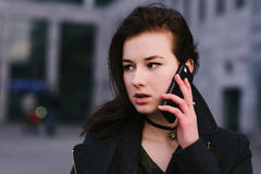 Portrait of a young beautiful and serious business woman brunette is talking on the phone on a city a dark background. Portrait of a young beautiful and serious Stock Photo