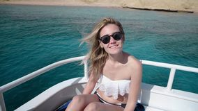 Portrait of a young beautiful sexy Caucasian woman on a yacht in bikini and sunglasses. The concept of vacation, freedom. Sunny summer stock video