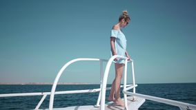 Portrait of a young beautiful sexy Caucasian woman on a yacht in in a blue dress and sunglasses. The concept of vacation. Freedom, sunny summer. Blue ocean on stock footage