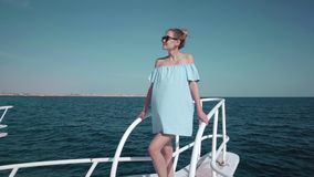 Portrait of a young beautiful sexy Caucasian woman on a yacht in in a blue dress and sunglasses. The concept of vacation. Freedom, sunny summer. Blue ocean on stock video